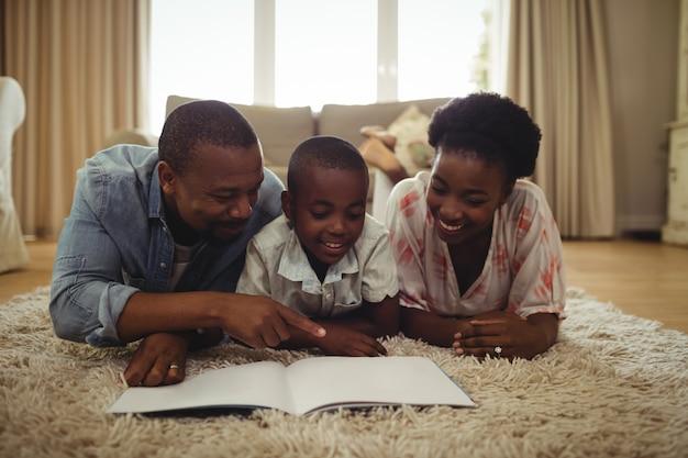 Eltern und sohn lesen ein buch, während sie auf einem teppich liegen