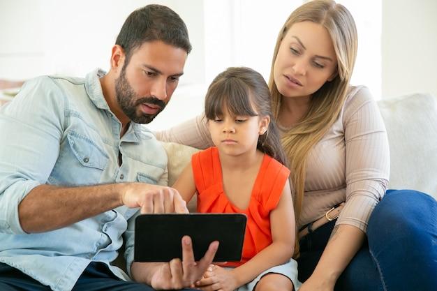 Eltern und süßes mädchen sitzen auf der couch, verwenden tablette, schauen video zusammen.