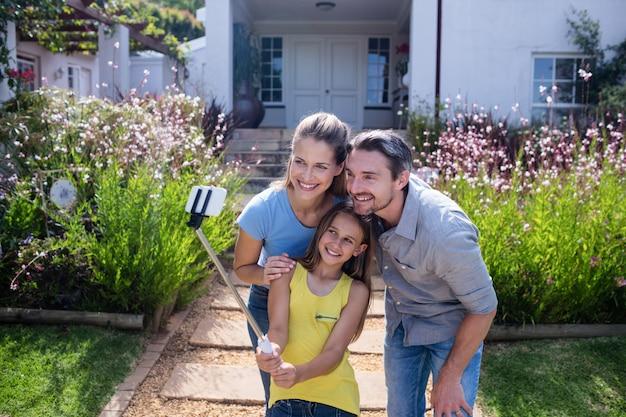 Eltern und tochter, die ein selfie mit selfie stock nehmen