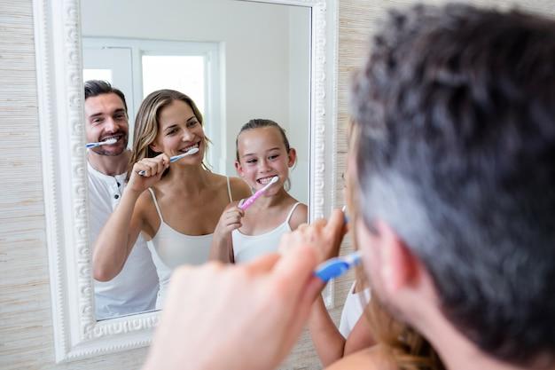Eltern und tochter, die ihre zähne im bad putzen