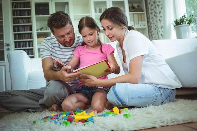 Eltern und tochter lesen ein buch, während sie mit bausteinen spielen