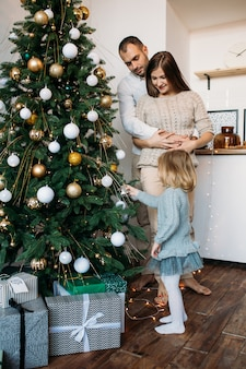 Eltern und tochter schmücken den weihnachtsbaum drinnen