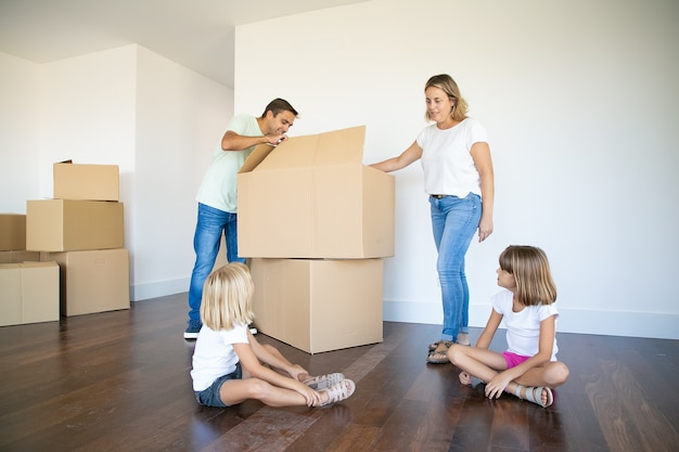 Eltern und zwei töchter öffnen kisten und packen dinge in ihrer neuen leeren wohnung aus