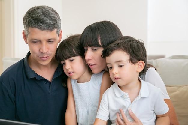Elternpaar und zwei kinder, die computer für videoanruf verwenden, zusammen auf der couch sitzen und anzeige betrachten