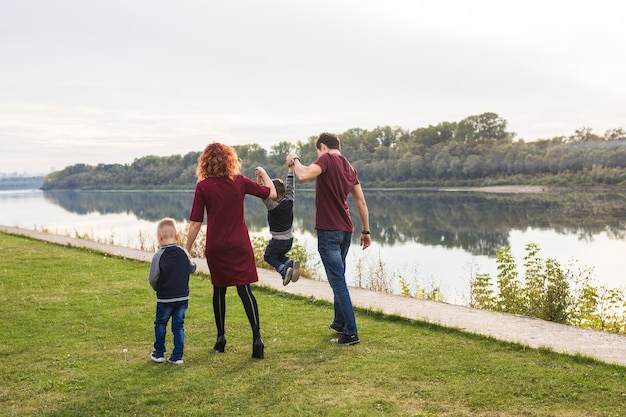 Elternschaft, kindheit, menschenkonzept - familie, die in der nähe des flusses spaziert.