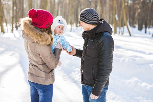 Elternschaft, mode, saison und menschenkonzept. glückliche familie mit kind in winterkleidung im freien.