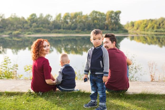 Elternschaft, natur, menschen konzept - familie mit zwei söhnen, die in der nähe des sees sitzen.