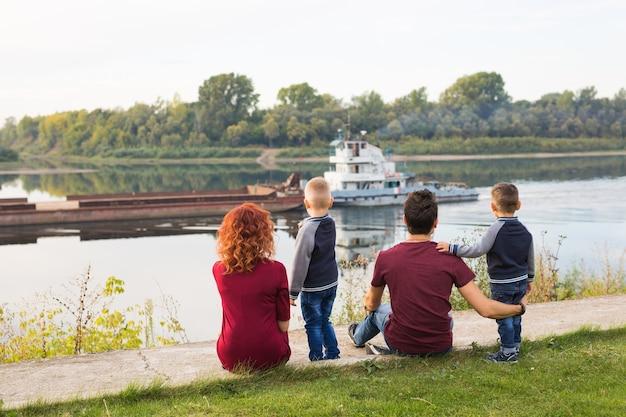 Elternschafts-, kindheits- und naturkonzept - familie, die auf dem grünen boden sitzt und klein betrachtet