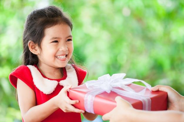 Elternteil, das dem netten asiatischen kindermädchen weihnachtsgeschenk gibt