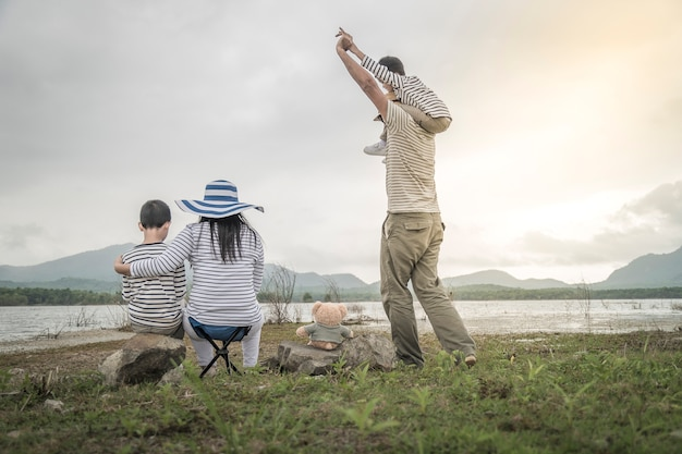 Elternteil mit jungen töchtern und sohn auf picknick nahe dem see