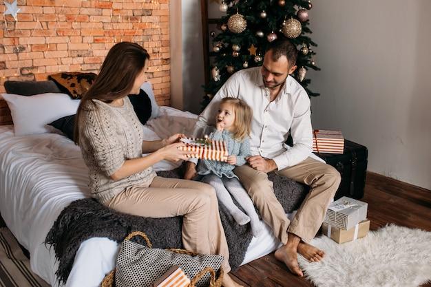 Elternteil und kleines kind, die spaß auf bett zu hause nahe baum haben