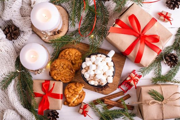 Emaillierte tasse heißen kakao oder kaffee mit marshmallows und keksen. um die äste, geschenke und brennende kerzen. weihnachtsstimmung. postkarte oder winterhintergrund.