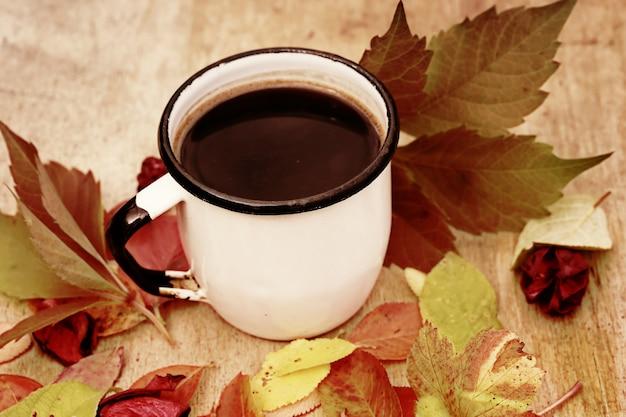 Emaillierter tasse kaffee mit retro- weinlese des zimtherbstlaubs