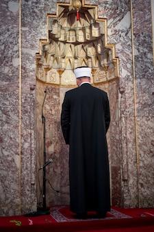 Emam in moschee mit versen aus kuran an der wand