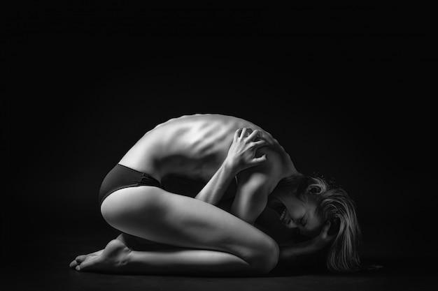 Embryoposition der jungen frau, die in der schwarzweiss-art aufwirft. das konzept von hilflosigkeit und einsamkeit.