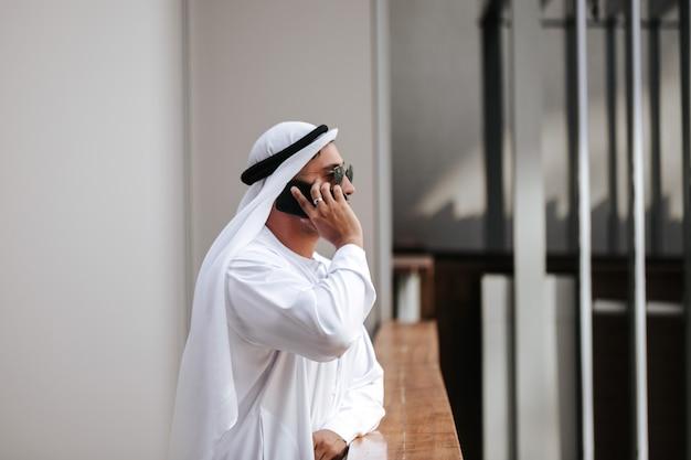 Emirati-typ, der traditionelle kandura in der städtischen stadt trägt, emiriert lebensstil, der mit smartphone spricht.