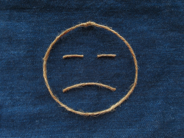 Emoji. trauriger smiley aus schnur auf blauem denim. nahansicht