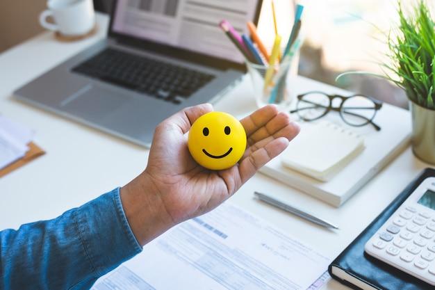 Emoticonball auf männlicher hand auf arbeitstischglückliche lebenskonzepteinspiration und motivationsidee