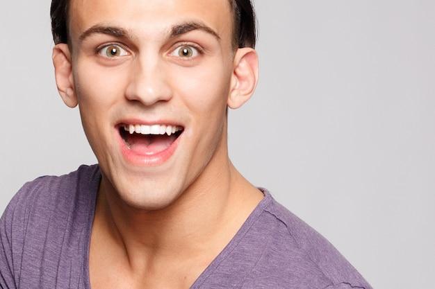 Emotion, werbung und people-konzept - hübscher junger mann auf grauem hintergrund, der die kamera betrachtet. porträt des sexy mannes. glücklicher kerl, der lächelt.