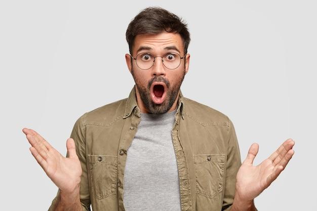 Emotional bärtiger junger mann mit überraschtem zweifelhaftem gesichtsausdruck umklammert verwirrt die handflächen und starrt mit ungläubigen augen