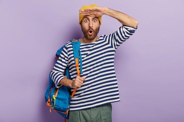 Emotional betäubter junger mann kann nicht an etwas glauben, hält handflächen in der nähe der stirn, trägt gelben hut und gestreiften pullover