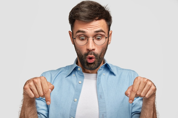 Emotional betäubter junger mann mit überraschtem gesichtsausdruck zeigt mit beiden zeigefingern nach unten, bemerkt etwas seltsames, hält die augen offen, trägt freizeitkleidung, isoliert über weißer wand