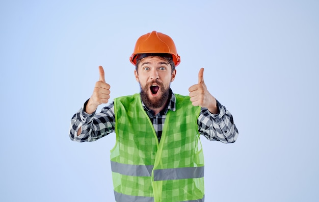 Emotional builder deutet mit den händen auf eine reflektierende weste mit orangefarbenem helm. hochwertiges foto