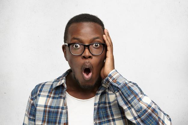 Emotional erstaunter oyung dunkelhäutiger mann in brille und kariertem hemd, der ungläubig den kopf berührt, überrascht und schockiert von positiven unerwarteten nachrichten. menschliche gesichtsausdrücke und emotionen