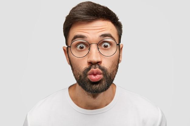Emotional gutaussehender junger mann starrt in die kamera, hält die lippen rund, schaut ungläubig, verzieht das gesicht