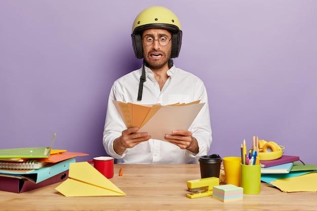 Emotional schockierter mitarbeiter, der am schreibtisch sitzt
