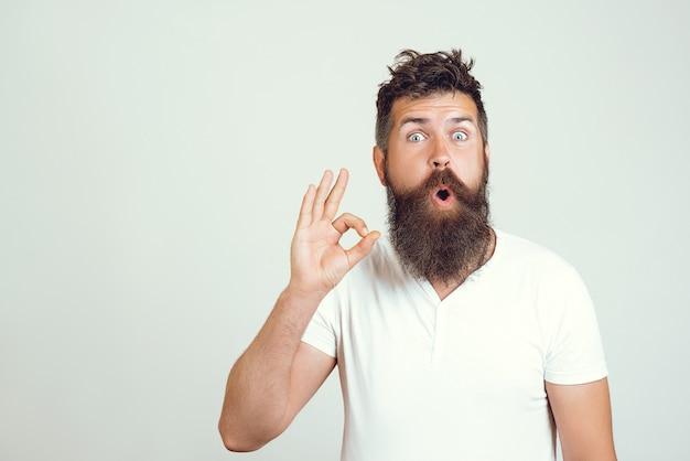 Emotional überrascht bärtiger mann zeigt ok zeichen mit beiden händen, zeigt seine zustimmung, zeigt, dass alles in ordnung ist, gesten gegen weiße wand. körpersprache und mimik. ausgezeichnet!