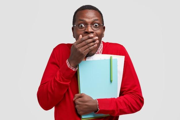 Emotional überrascht dunkelhäutiger junger mann bedeckt mund mit handfläche, hat freudigen ausdruck, erhält ausgezeichnete note bei der prüfung, trägt lehrbuch, papiere eng