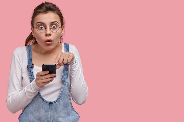 Emotional überraschte junge frau kann nicht an verkäufe und rabatte im webshop glauben, zeigt auf den bildschirm des smartphones, ist erstaunt über die erhaltene benachrichtigung
