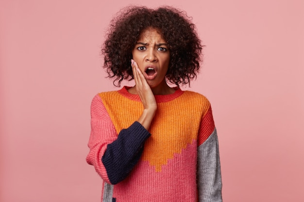 Emotionale afroamerikanerfrau mit afro-frisur, die etwas schrecklich schreckliches schreckliches ekelhaftes betrachtet, öffnete mund vom schock, gelehnte hände auf gesicht, tragenden bunten pullover, isoliert auf rosa