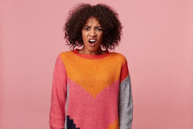 Emotionale afroamerikanerfrau mit afro-frisur, die etwas schrecklich schreckliches schreckliches ekelhaftes betrachtet, runzelt die stirn, trägt buntes pullover, isoliert