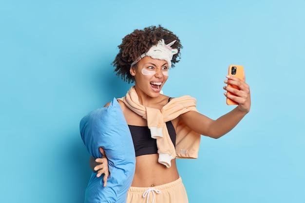 Emotionale afroamerikanerin ruft wütend aus, während selfie auf dem smartphone sich auf die schlafenszeit vorbereitet