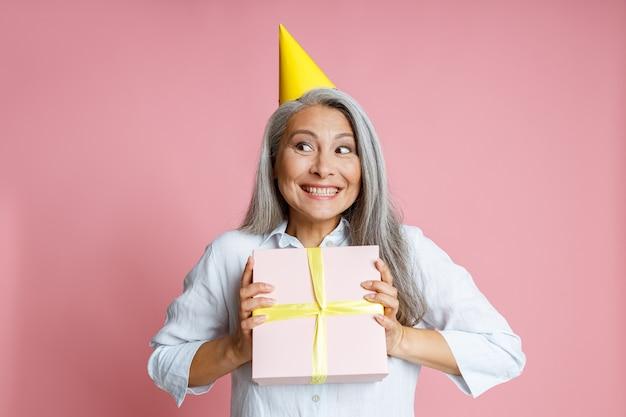 Emotionale asiatische frau mit lockerem grauem haar und partyhut hält geschenk auf rosa hintergrund