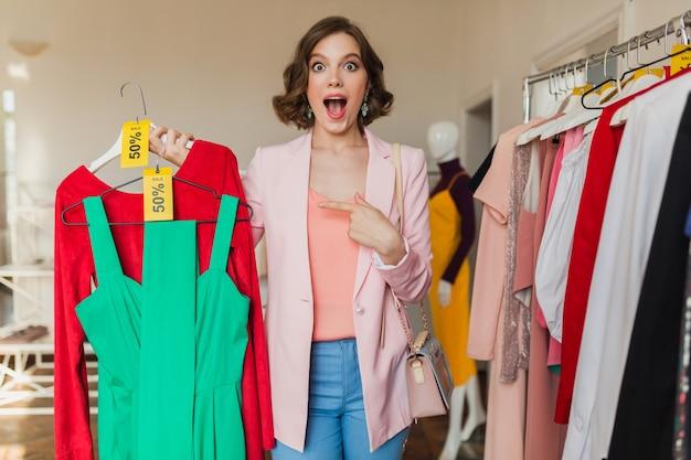 Emotionale attraktive frau, die bunte kleider auf kleiderbügel im bekleidungsgeschäft hält