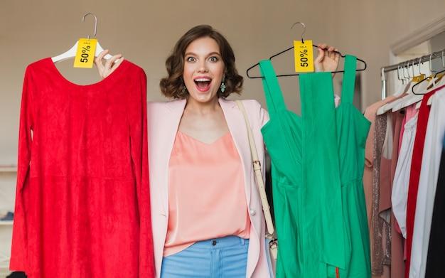 Emotionale attraktive glückliche frau, die bunte kleider im bekleidungsgeschäft hält