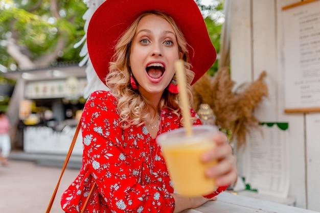 Emotionale attraktive stilvolle blonde lächelnde frau in strohrotem hut und bluse sommermode-outfit, das natürlichen fruchtcocktail-smoothie trinkt