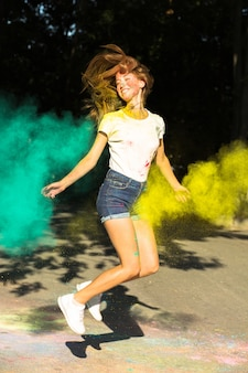 Emotionale blonde frau, die mit leuchtenden farben springt, die um sie herum explodieren