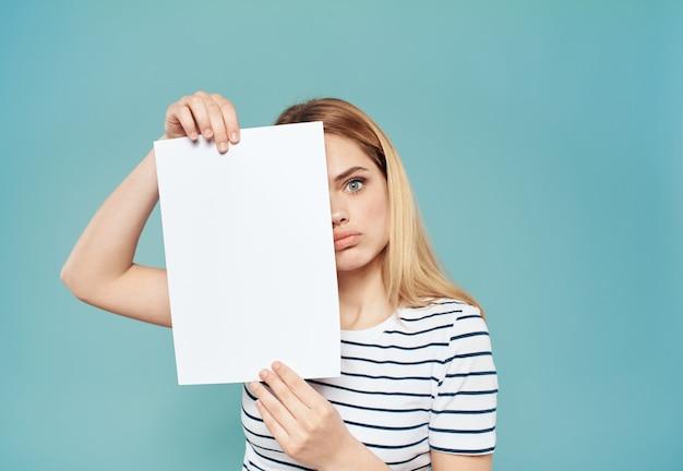 Emotionale blonde frau mit einem weißen blatt papier in ihren händen auf einer blauen wand