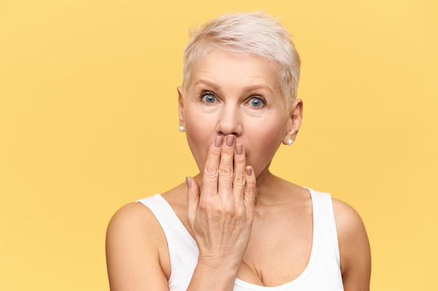 Emotionale blonde frau mittleren alters, die die augen weitet und den mund mit der hand bedeckt, versucht, keine faszinierenden informationen oder geheimnisse zu verraten, nachdem sie den erstaunten gesichtsausdruck überrascht hat