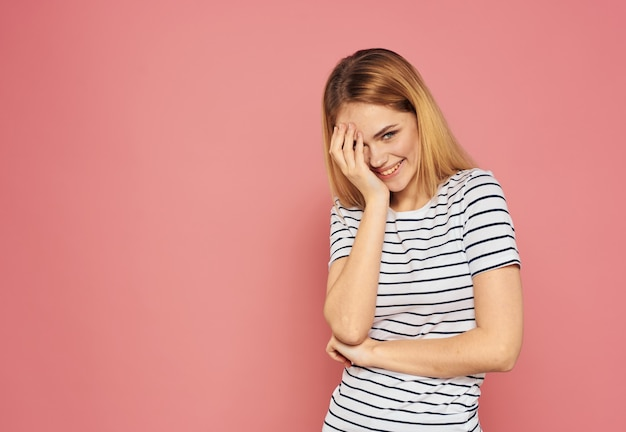 Emotionale blondine in einem gestreiften t-shirt gestikuliert mit ihren händen auf einem rosa