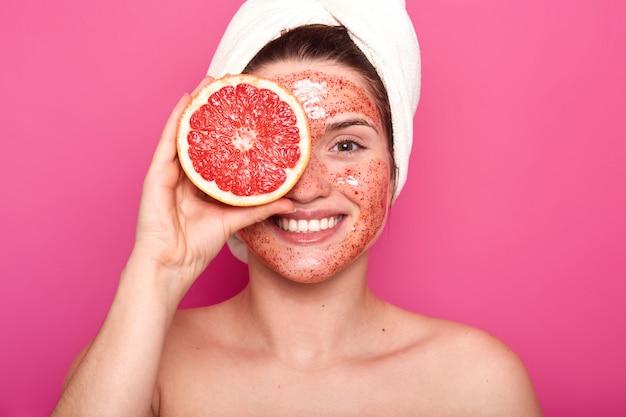 Emotionale charismatische junge frau mit einem schönen lächeln im gesicht verbringt zeit mit schönheitsbehandlungen, macht ihre haut frisch und sauber, hält die hälfte der grapefruit mit weißem handtuch auf dem kopf.