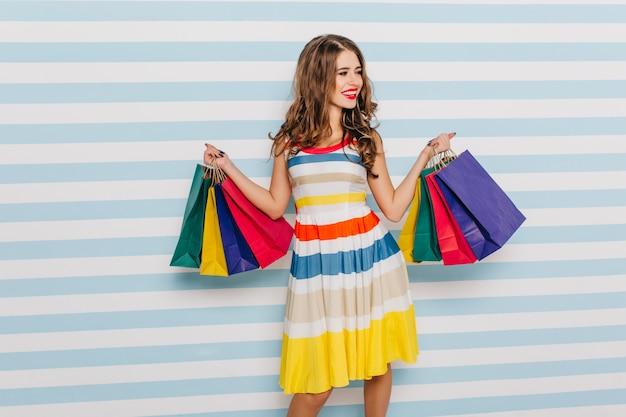 Emotionale dame in hellem, stilvollem, kurzem kleid sehen neuen pullover im laden. foto des mädchens in voller länge mit paketen auf blauer und weißer wand