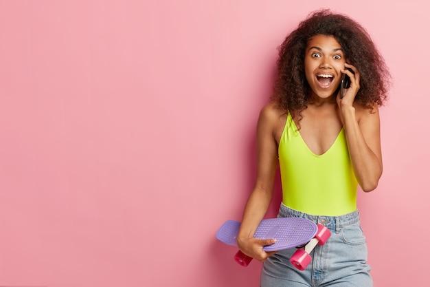 Emotionale dunkelhäutige frau spricht per handy, erzählt neuigkeiten an freunde, trägt ein modisches sommeroutfit, hält longboard, steht an der rosa wand, kopiert platz beiseite. lifestyle-konzept