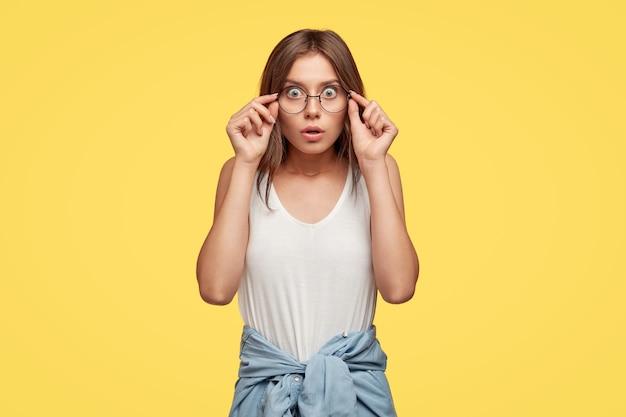Emotionale entsetzte junge brünette mit brille, die gegen die gelbe wand aufwirft