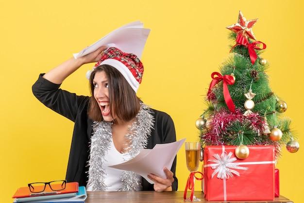 Emotionale erschöpfte geschäftsdame im anzug mit weihnachtsmannhut und neujahrsdekorationen, die dokumente halten und an einem tisch mit einem weihnachtsbaum darauf im büro sitzen