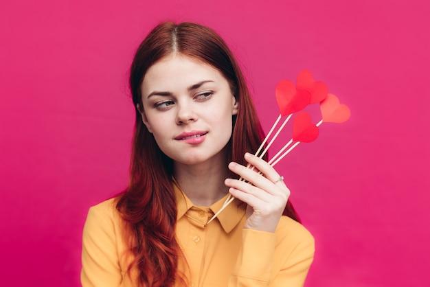 Emotionale frau des valentinstags mit papierherzen auf stick auf rosa hintergrund und modehemd